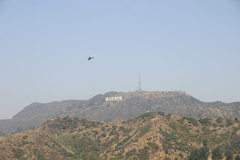 Black and white helicopter flying over green and brown mountain during daytime