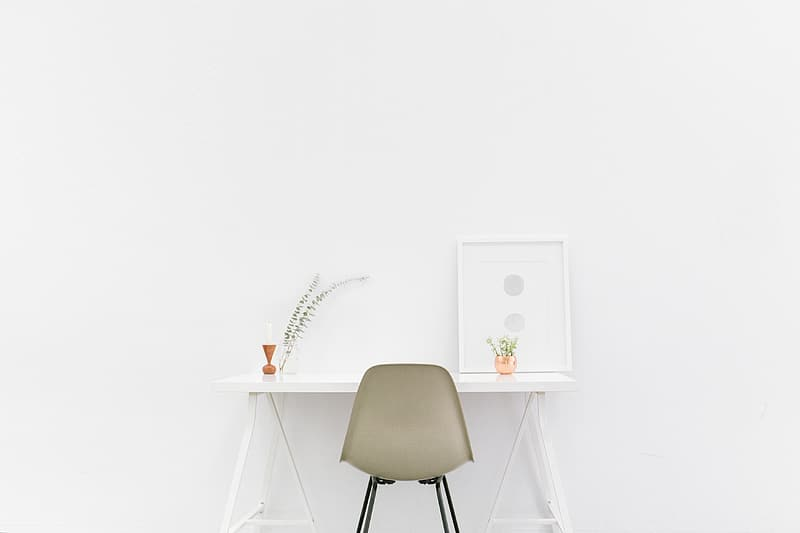 Gray armless chair and white wooden side table