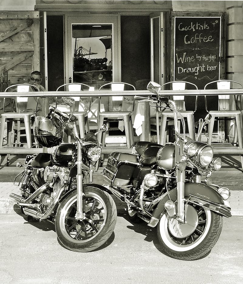 Two cruiser motorcycles parked in front of cafe