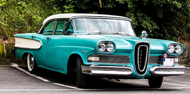 Teal and white sedan parked in parking lot