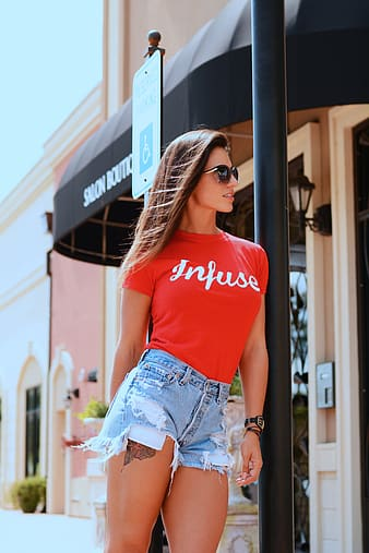 Woman wearing red infuse shirt and blue denim cutoff shorts