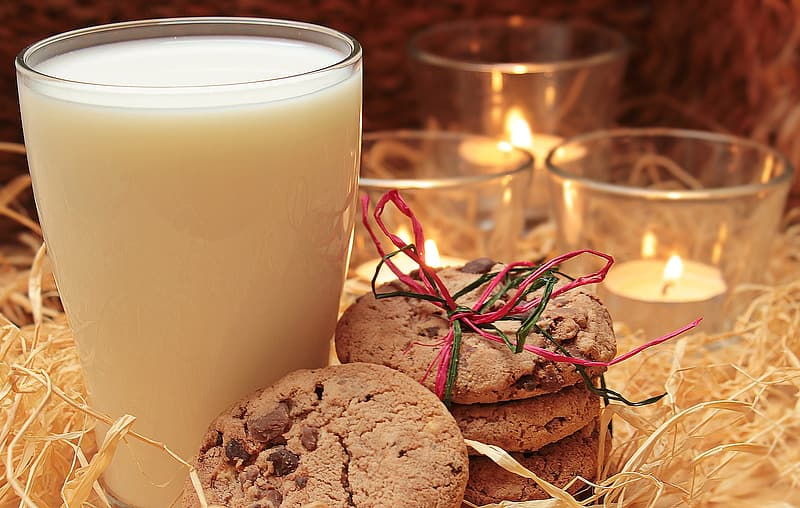Clear drinking glass filled with milk near candles