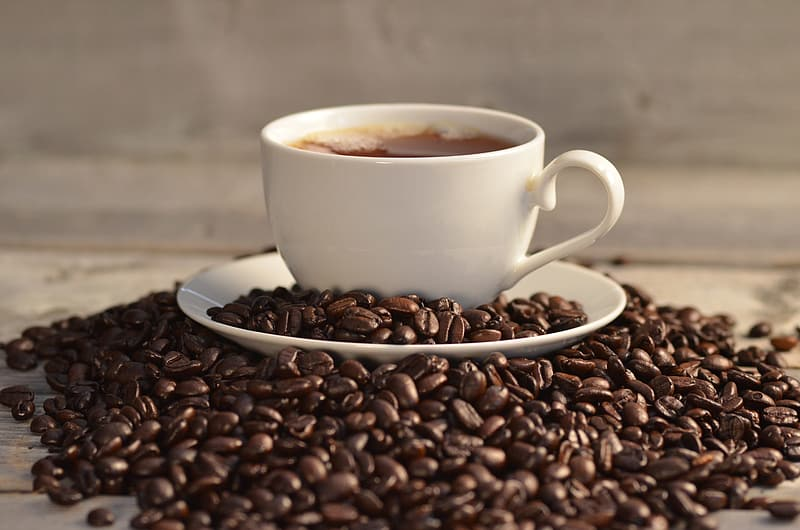 White mug surrounded by coffee beans