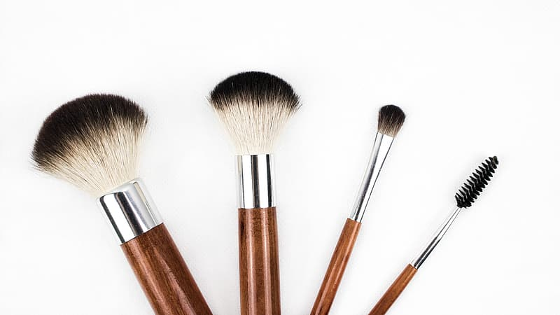 Four brown makeup brushes with white background