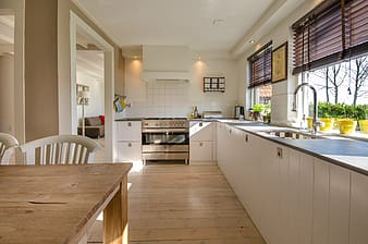 Brown wooden dining table beside white wooden kitchen cabinet