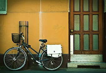 Bicycle parked beside orange wall and door