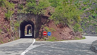 Gray tunnel near concrete road at daytime