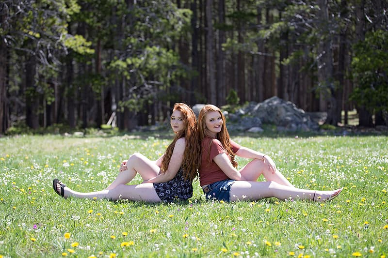 Two woman sitting on grass