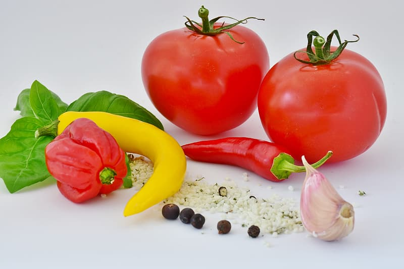 Two red tomatoes beside red chili and bell pepper