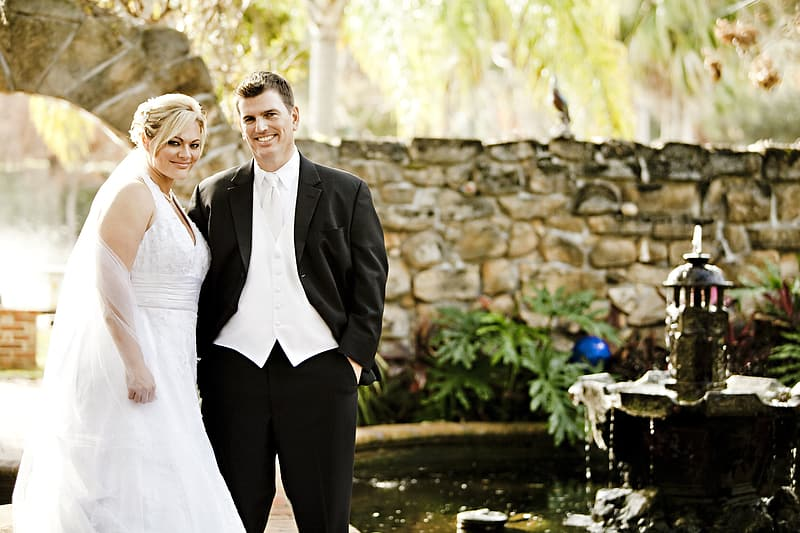 Man in black suit and woman in white wedding dress standing near garden fountain during daytime