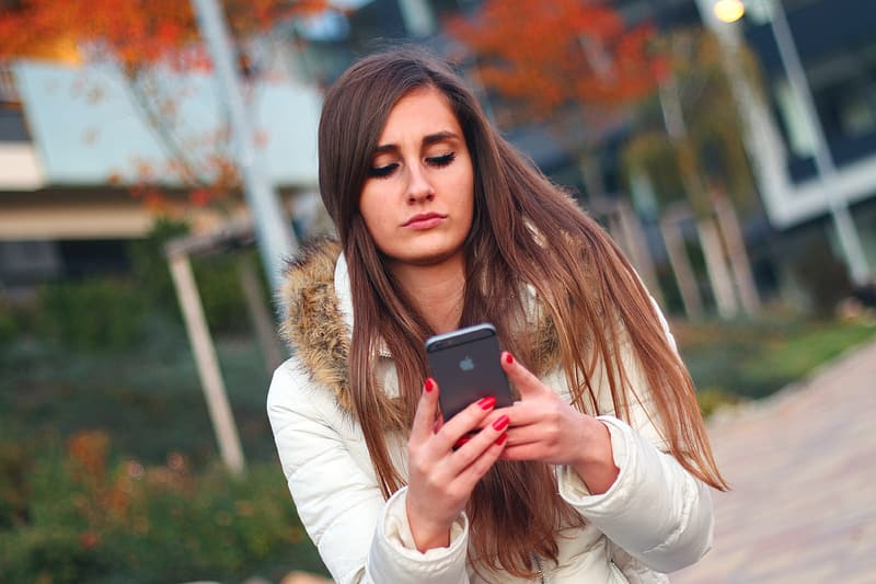 Woman in white jacket holding black smartphone