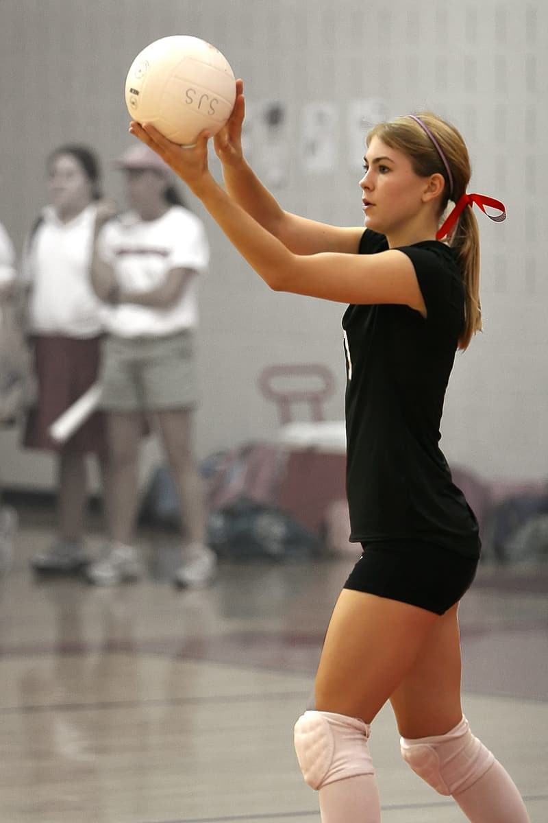 Woman serves volleyball