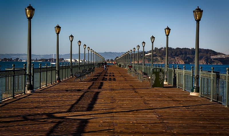 Brown wooden pier with black lamp post on each side