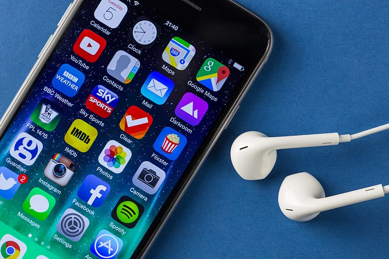 Close-up shot of the iPhone 6 mobile smartphone and earphones on a plain blue background
