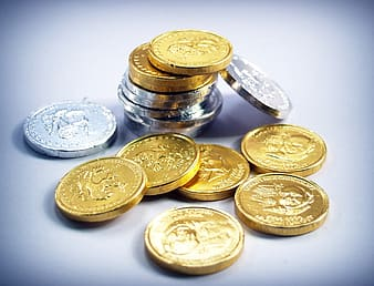 Close-up photo of silver-colored and gold-colored coin lot on white surface