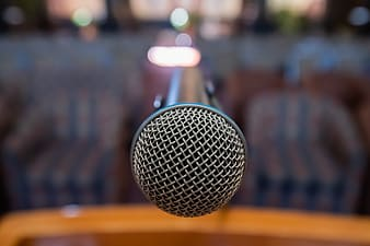Black microphone on brown wooden table