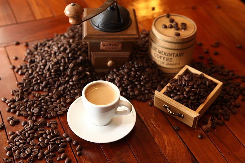 Cup of coffee beside coffee beans and coffee grinder