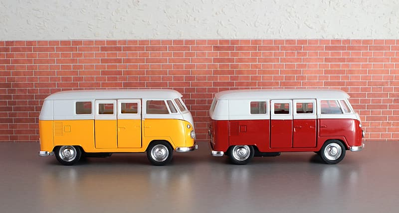 Two white, red, and yellow die-cast metal van scale models on gray concrete surface