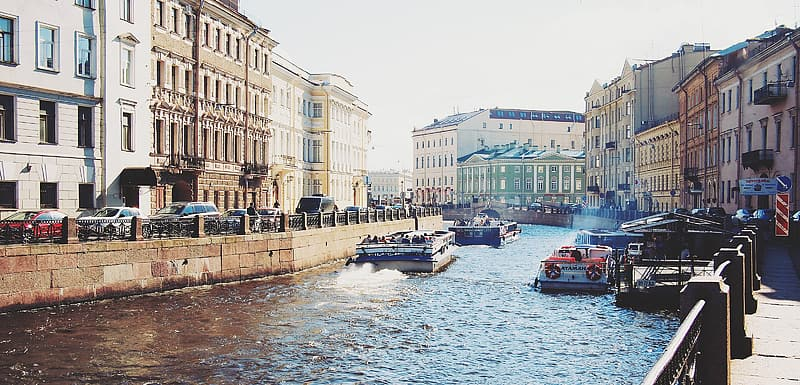Ferries maneuvering on canal between buildings during daytime
