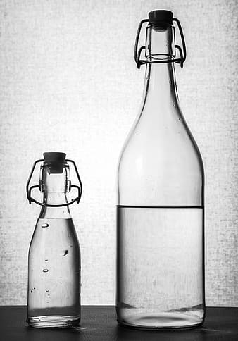 Two glass bottles with clear liquid inside