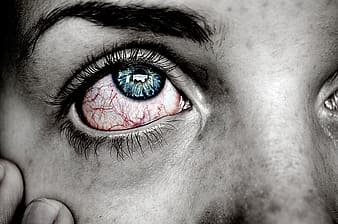 Selective color photography of person with bloodshot eyes and blue iris