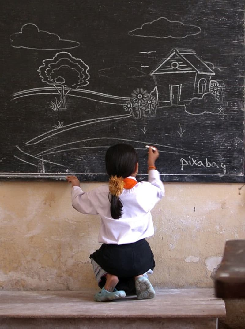 Girl draw a house on chalkboard