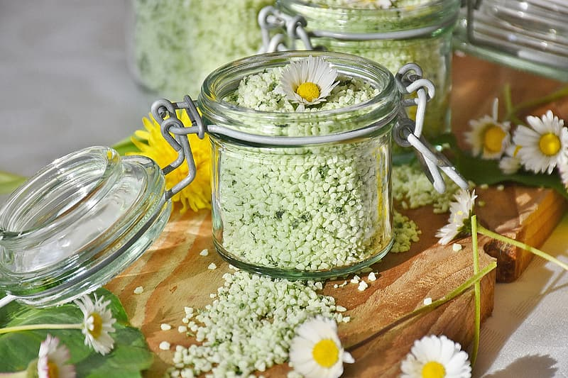 Clear glass jar with lid and daisy flowers