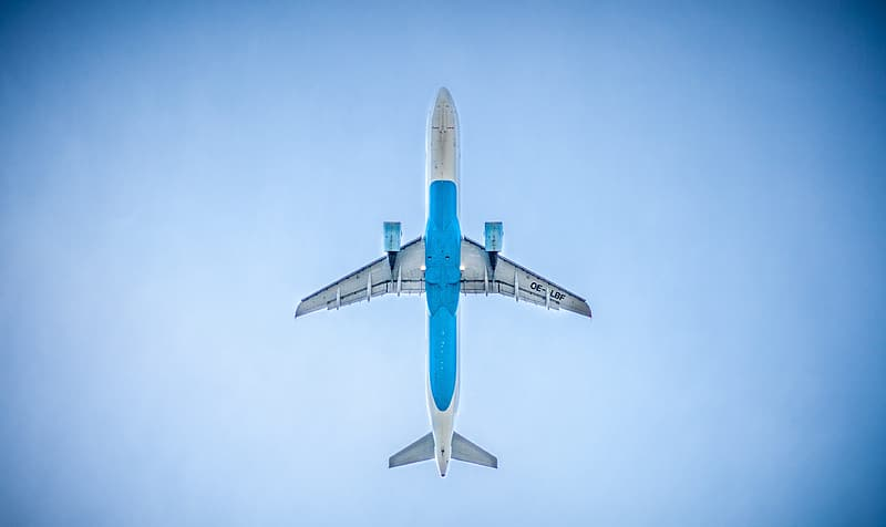 White and blue airplane in mid air during daytime
