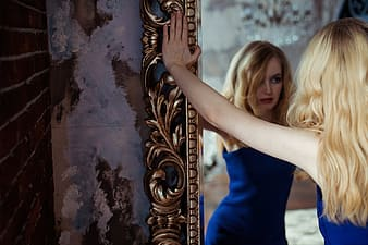 Woman wearing blue sleeveless shirt holding the frame of a mirror