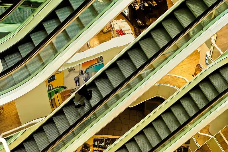 Person on gray escalator at inside building