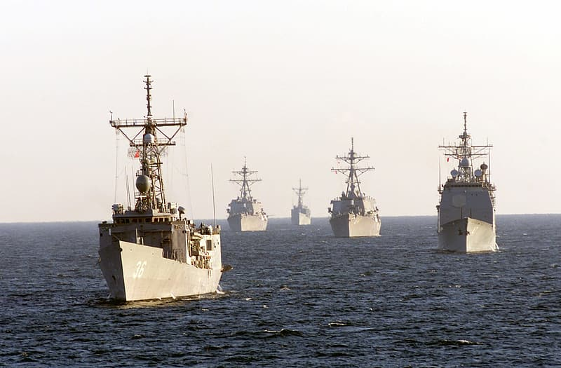Five brown fighting ships on sea