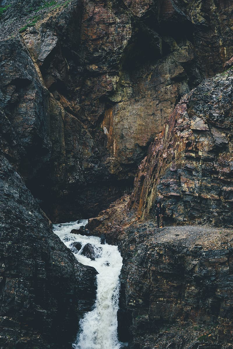 Time-lapse photography of waterfalls surrounded with black and brown rock formations