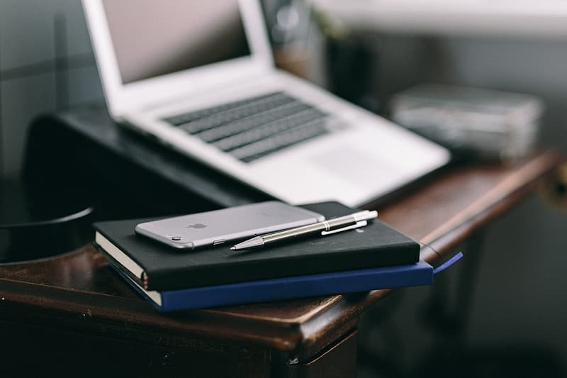 Elegant workspace with Macbook, iPhone, business cards and notebooks