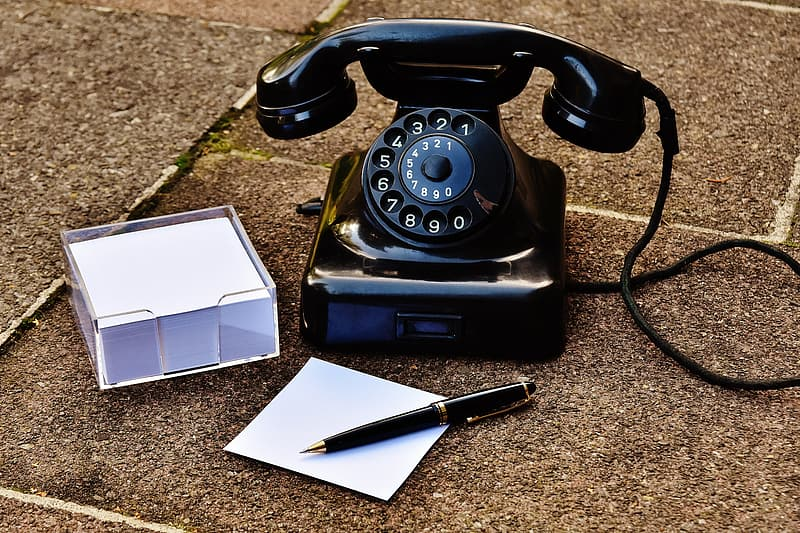 Rotary phone on ground beside pen and sticky note