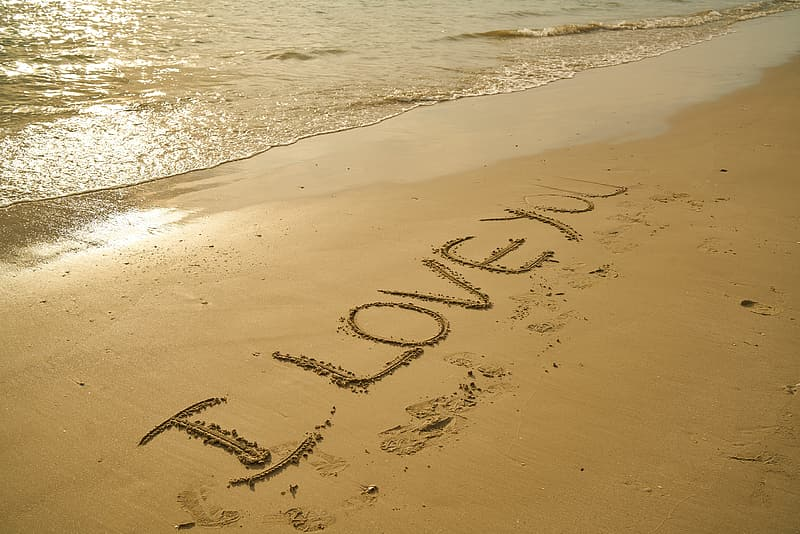 Photo of I Love You text written on sand in seashore
