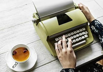 Person using gray typewriter beside white ceramic mug with brown liquid