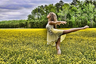 Woman dancing on yellow rapeseed flower field during daytime