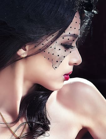 Woman in red lipstick and black polka-dot mesh headdress