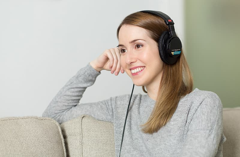 Woman wearing black corded headphones while sitting on sofa