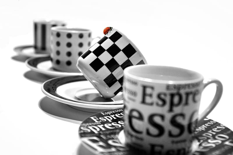 Selective focus photography of white and black checked ceramic teacup on saucer
