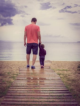 Father and child walking on wooden dock