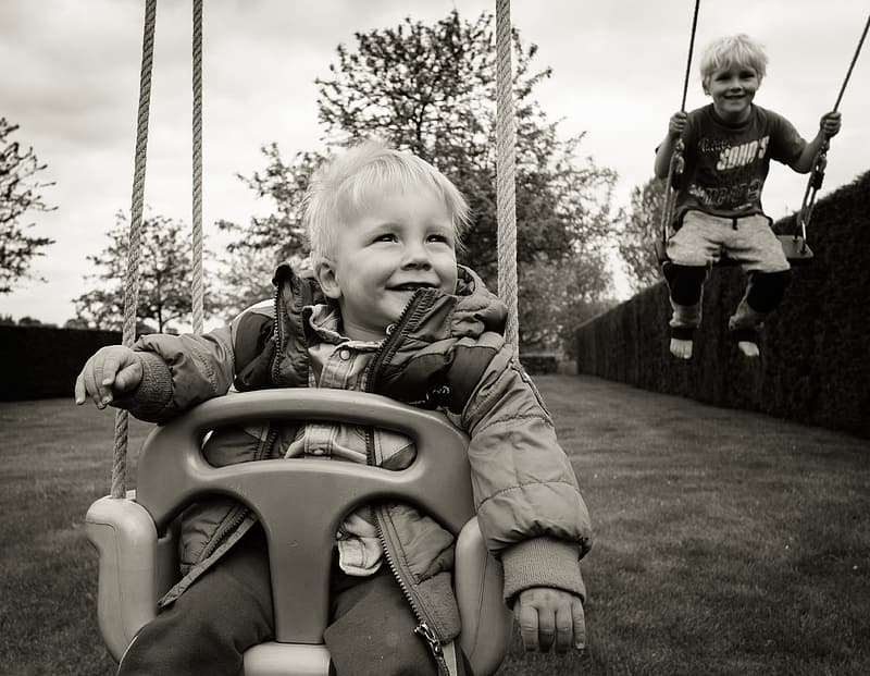 Grayscale photo of two children riding swing chairs