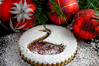 Three red christmas baubles beside pie