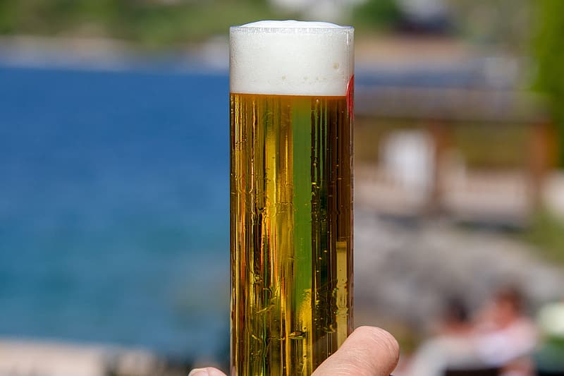 Clear drinking glass with beer in tilt shift photography