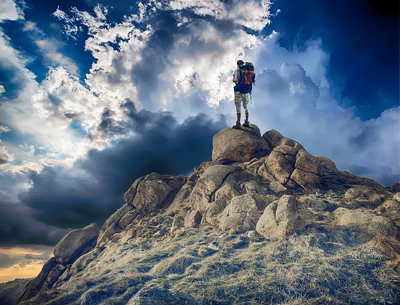 Person with hiking standing on stone on top of hill