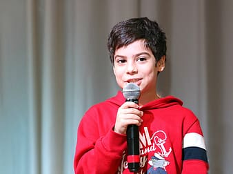 Boy wears red hoodie and holds talking white holding black microphone