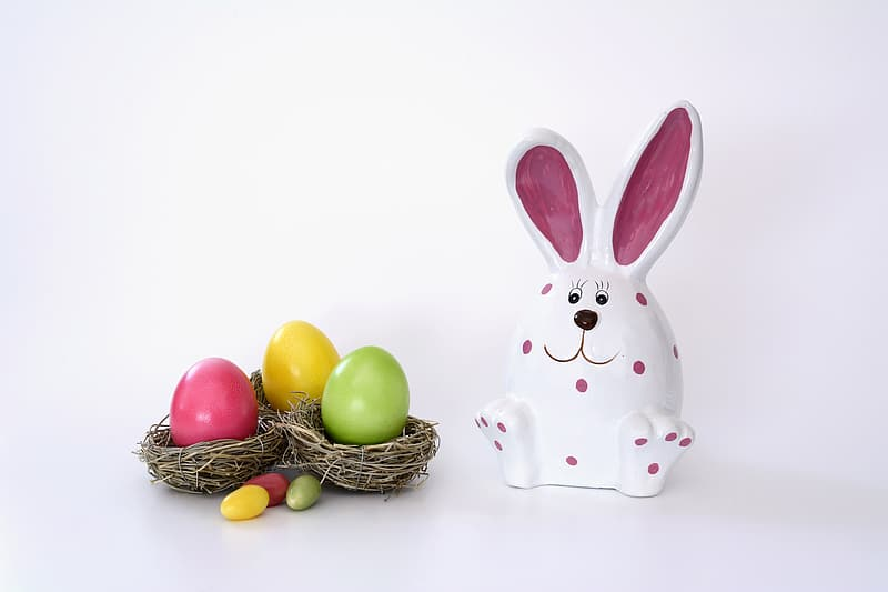 White and pink rabbit ceramic figurine beside Easter eggs