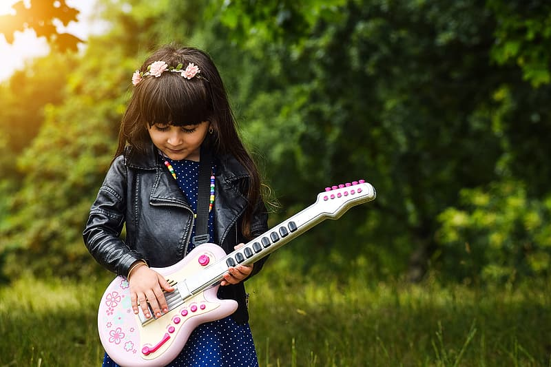 Shallow focus photography of girl holding guitar