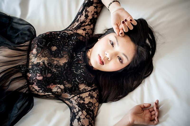 Woman lying on white bed sheet