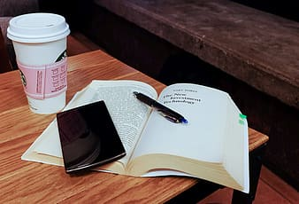 Open book and black smartphone
